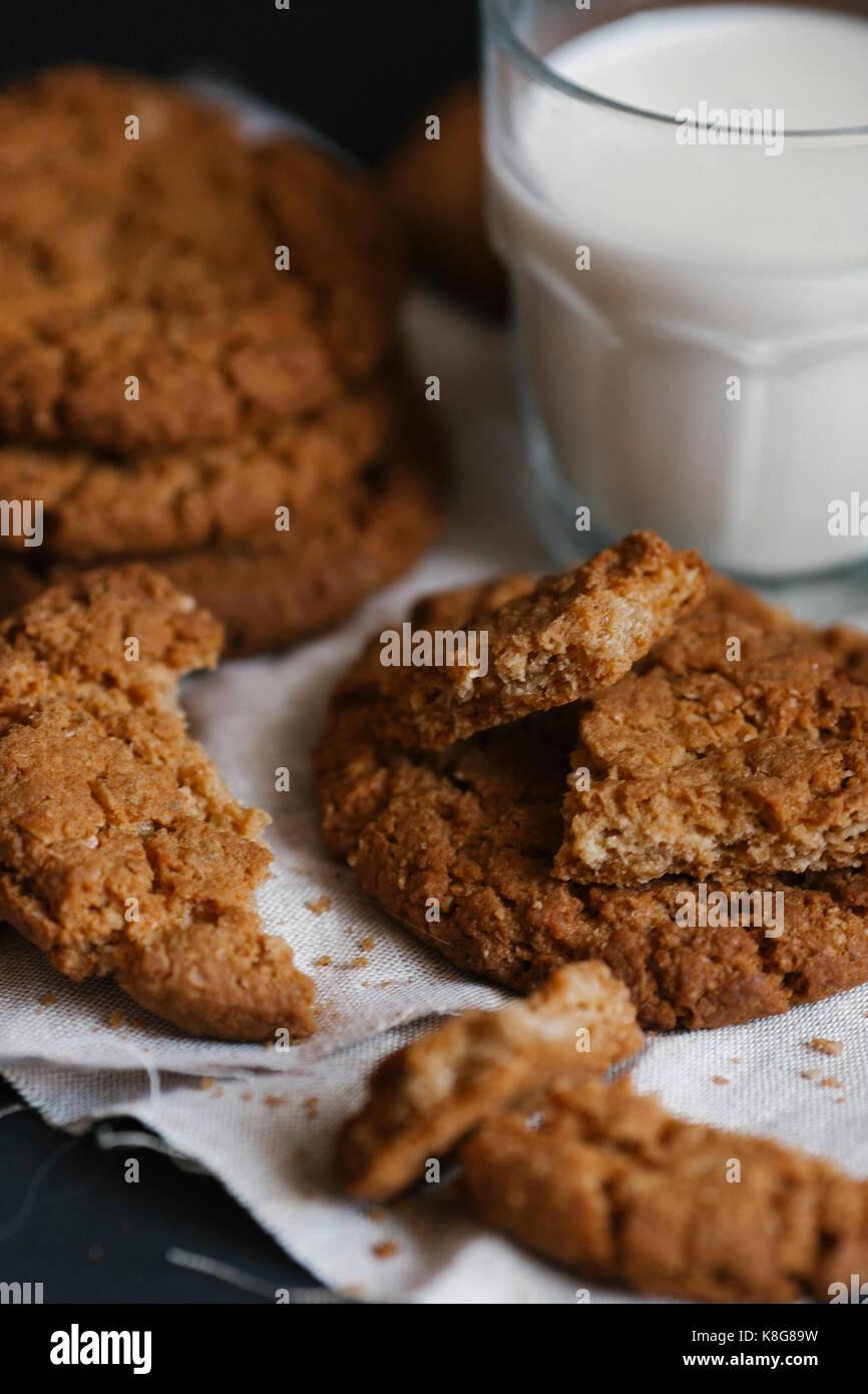 Un alto ángulo de visualización de comerse las galletas y leche en la mesa Imagen De Stock