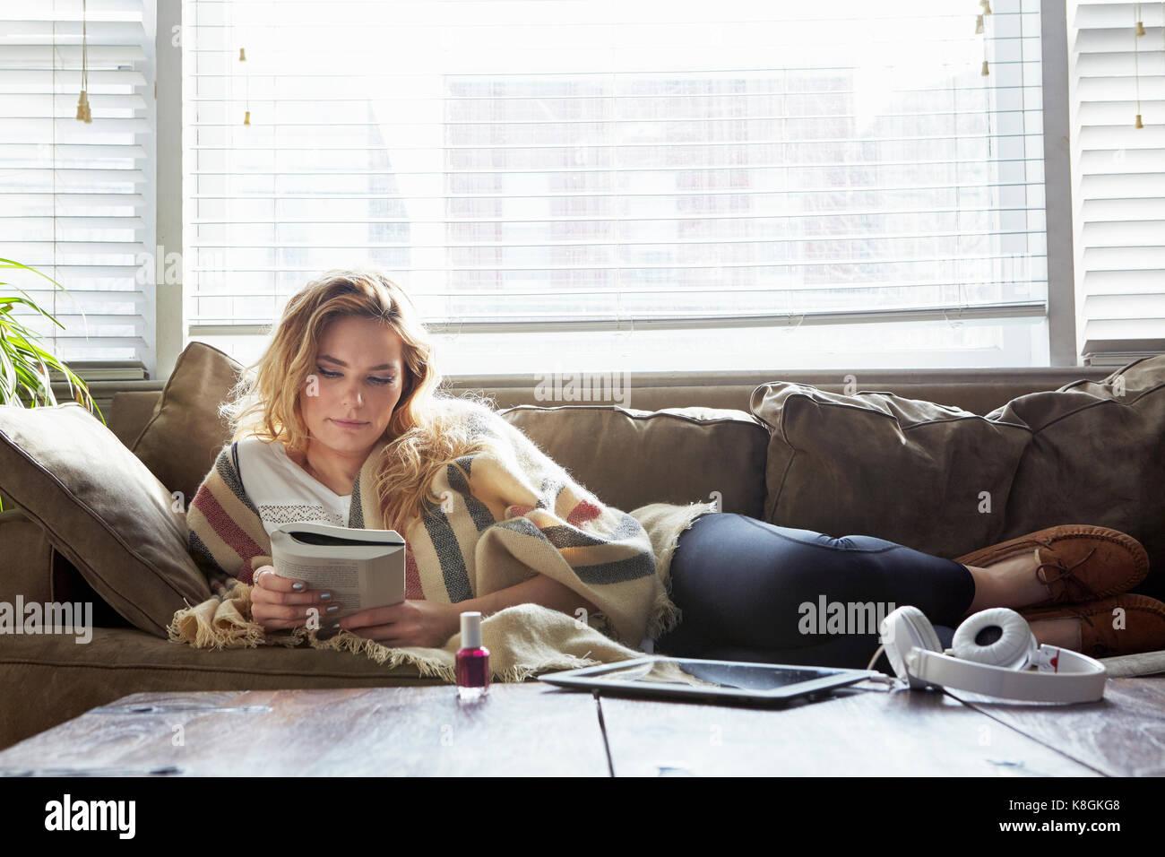 Mujer leyendo el libro sobre el sofá Foto de stock
