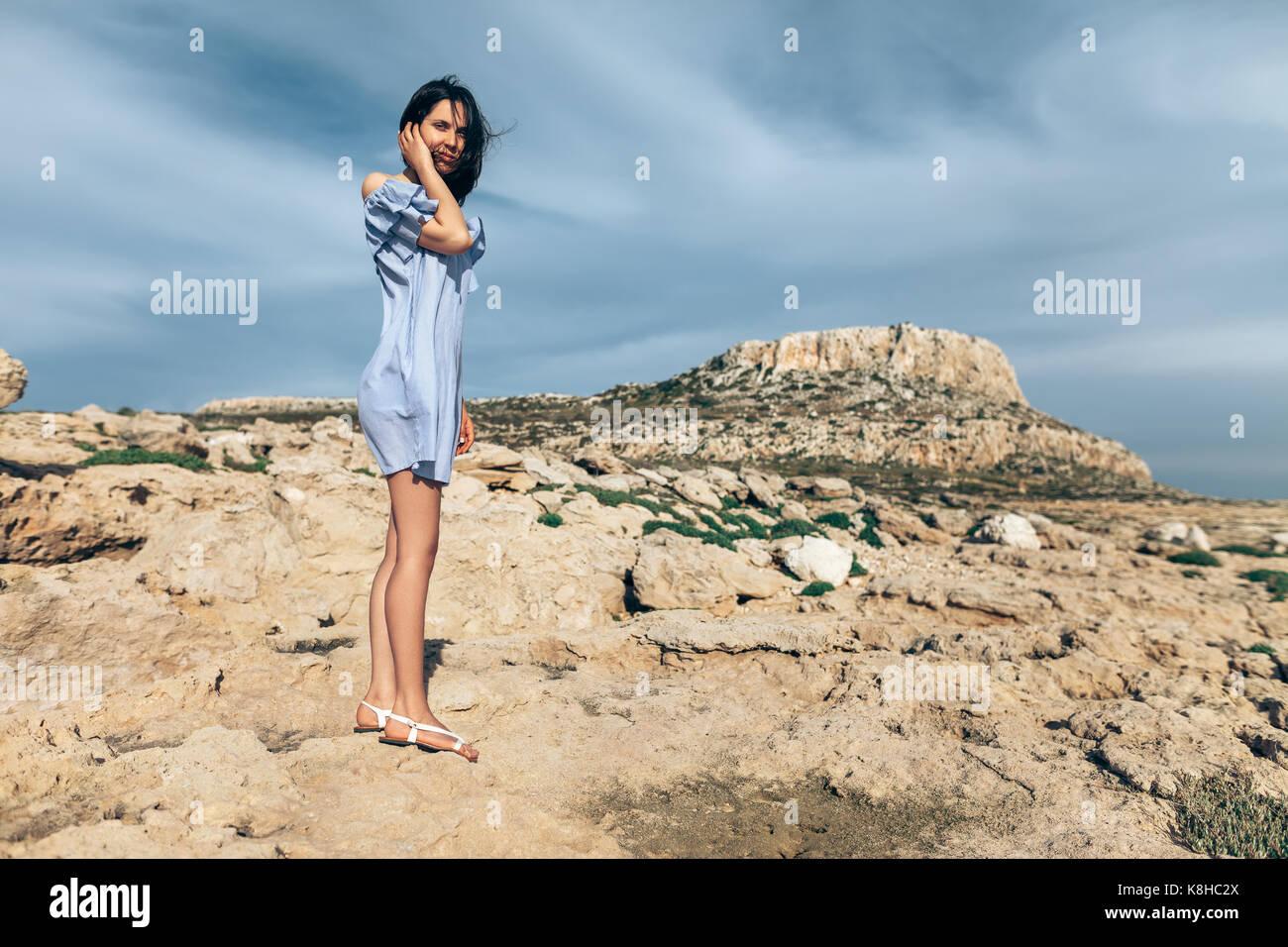 Hermosa Mujer de pie sobre un desierto rocoso con espectacular cielo. La moda Imagen De Stock