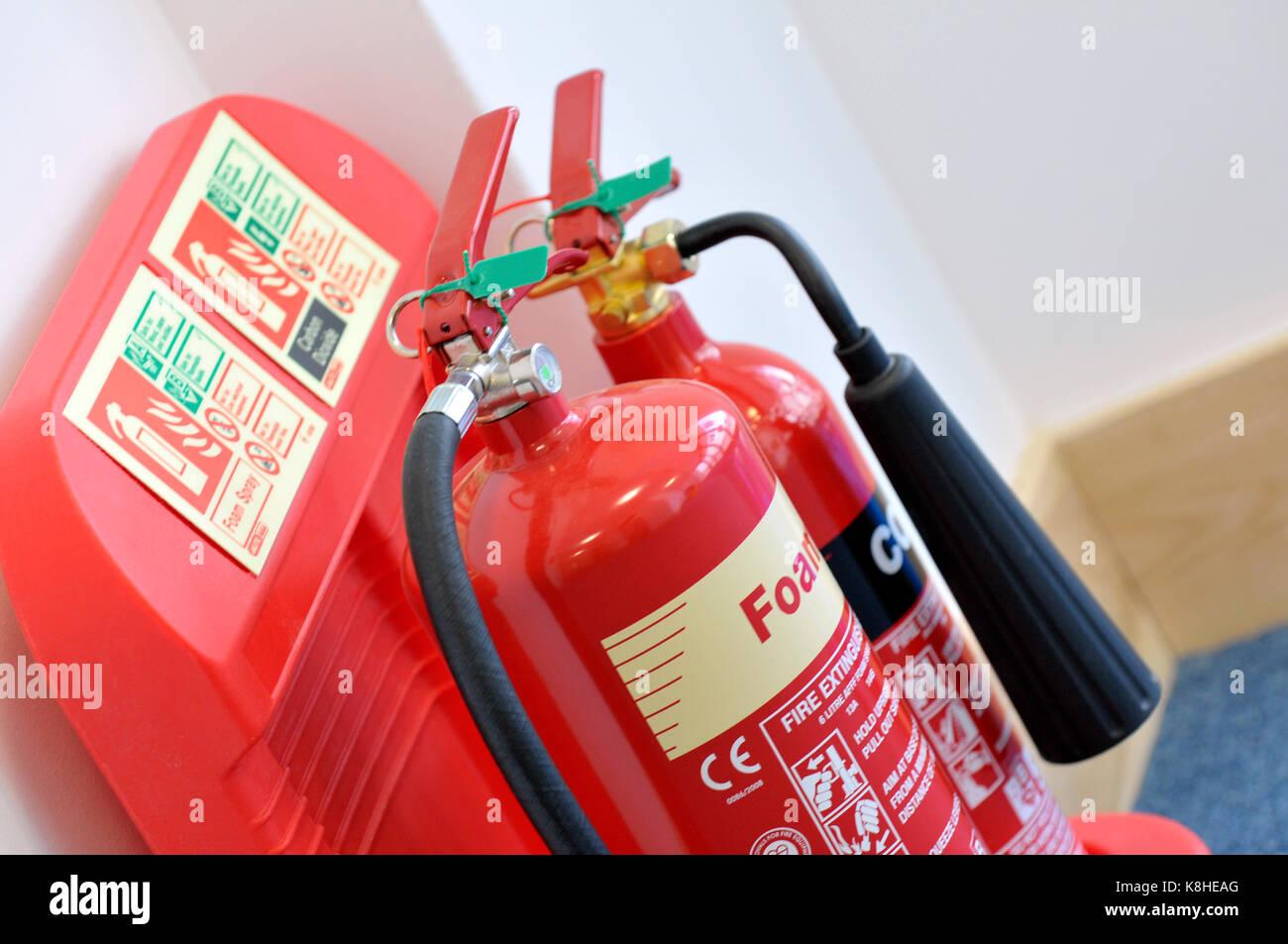 Dos extintores de incendios en un soporte especialmente diseñado en la pared de un edificio de oficinas. Espuma Imagen De Stock