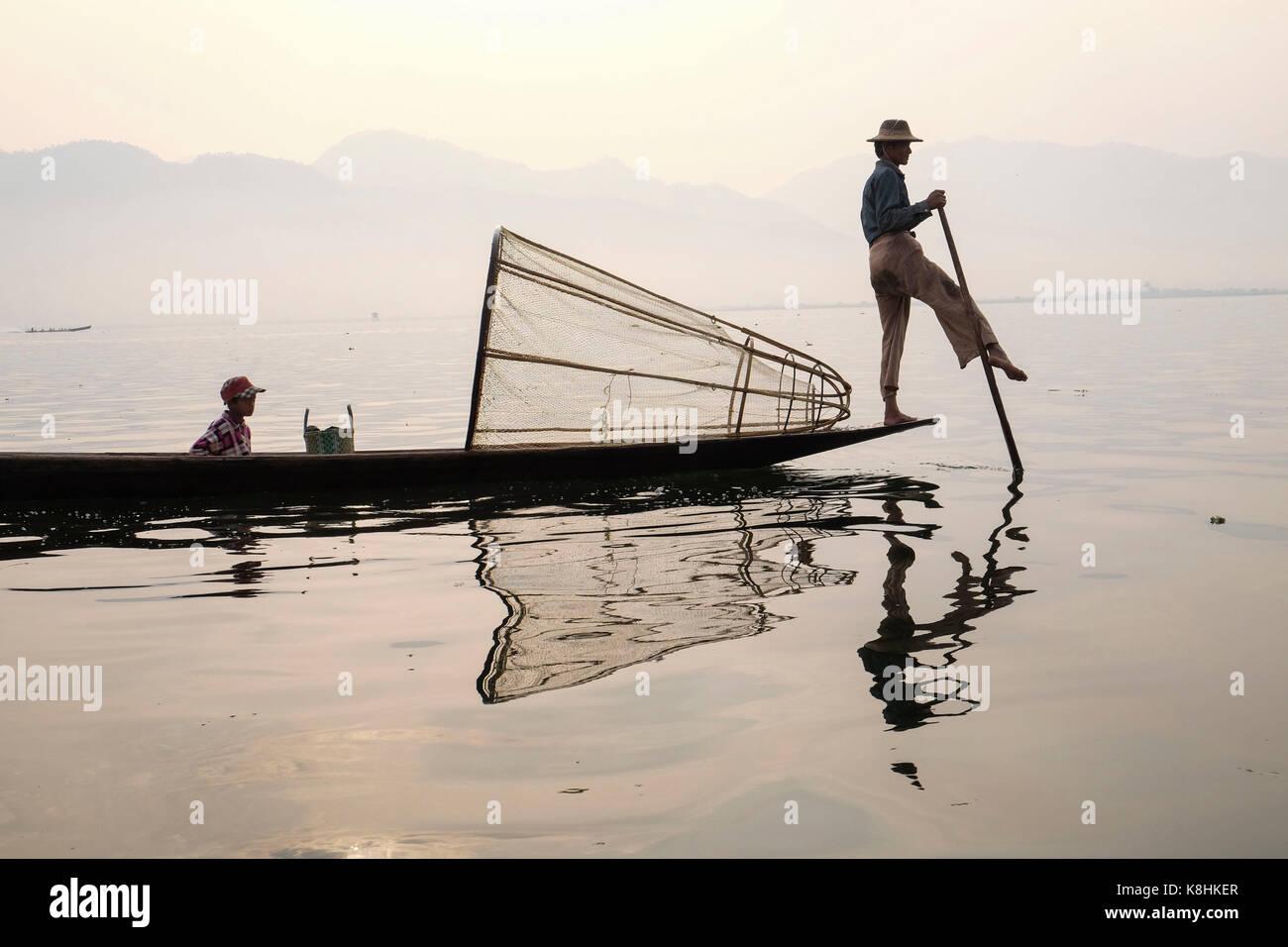 Birmania, Myanmar: pescador en una barcaza en el Lago Inle. Pescador con su hijo en una barcaza y cono de trampa de peces Foto de stock