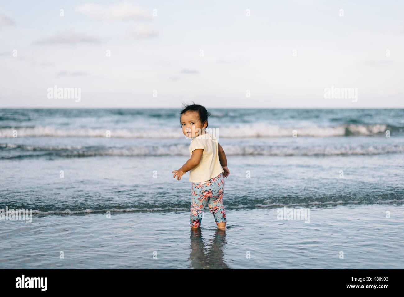 Bebé o niño jugando en la playa por primera vez ondas haciendo cara curiosa.aprendizaje.Concepto de crianza Imagen De Stock