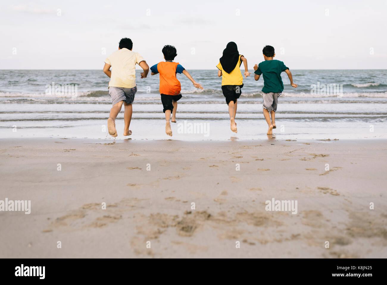 Niños corriendo en la playa juntos.amistad concepto.Concepto de familia.Concepto de vacaciones Imagen De Stock