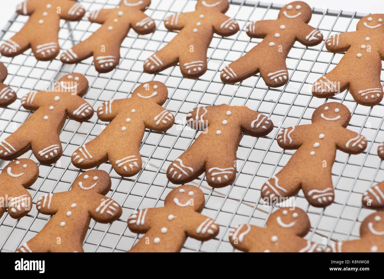 Hombres de pan de jengibre las galletas sobre una rejilla metálica. Uno donde la cabeza se ha comido Imagen De Stock