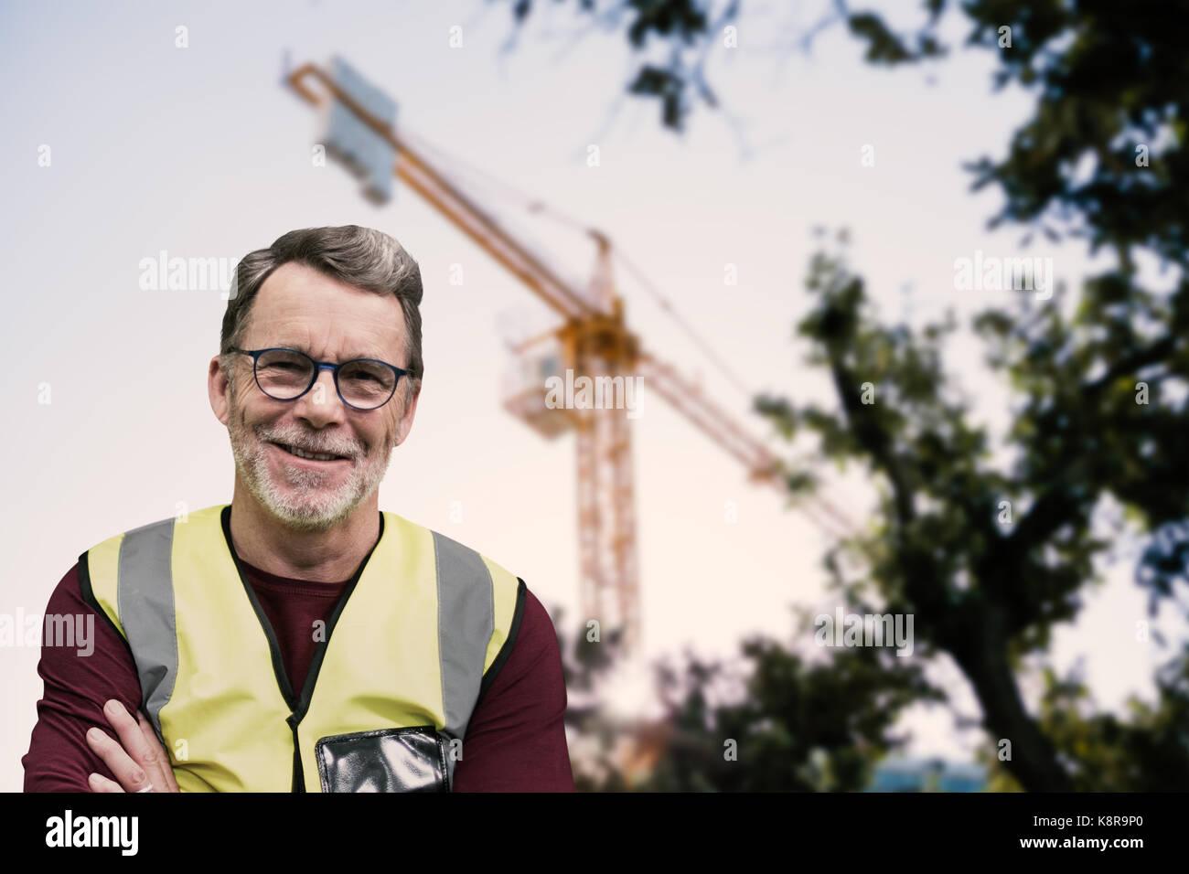 Retrato de ingenio trabajador senior de brazos cruzados vistiendo ropa reflectante contra la opinión de una grúa Foto de stock