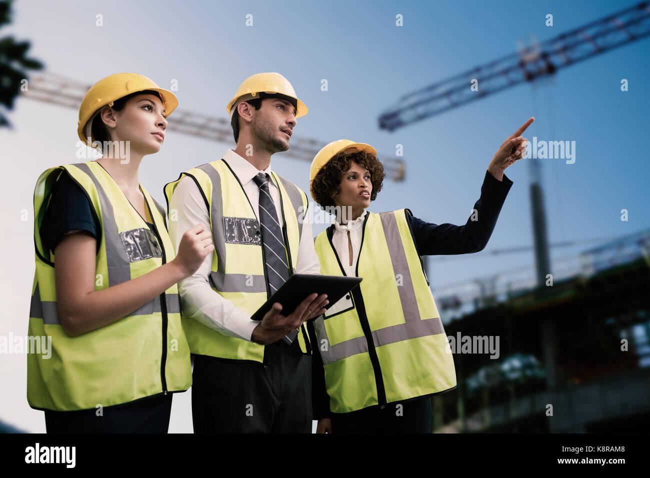 Arquitectos en ropa reflectora mirando a otro lado mientras Tablet PC contra la grúa y sitio de construcción Foto de stock