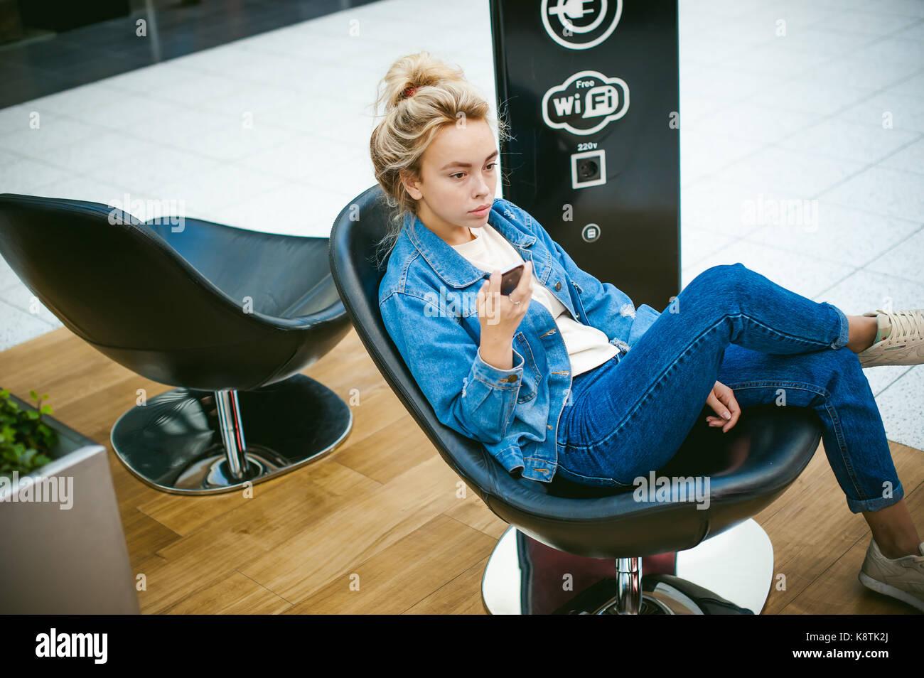 Hermosa mujer joven en jeans de ropa en el espacio de negocios de centro  comercial. el retrato de una niña con pecas en su rostro a95aa33b668