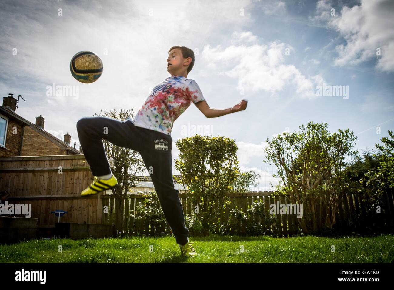 Chico jugando al fútbol en casa Foto de stock