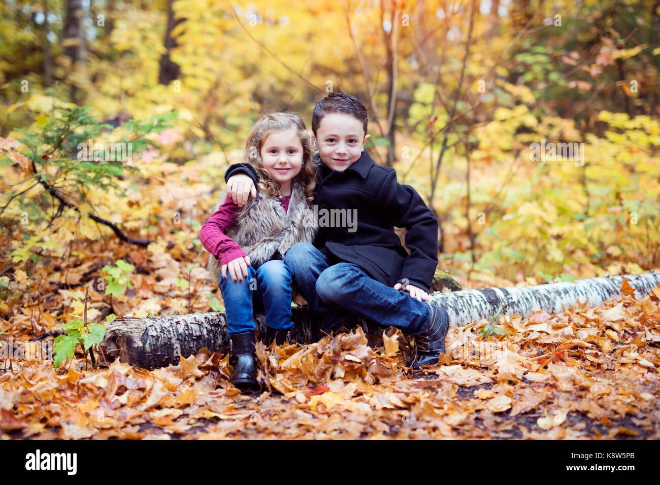 Niños jugando en un hermoso parque de otoño en frío soleado día de otoño. Imagen De Stock