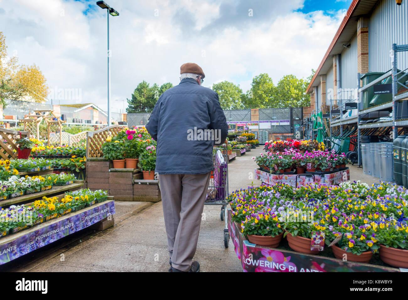 Ancianos jubilados hombre caminando con un carrito de la compra en la sección de jardín en plena floración en el Foto de stock