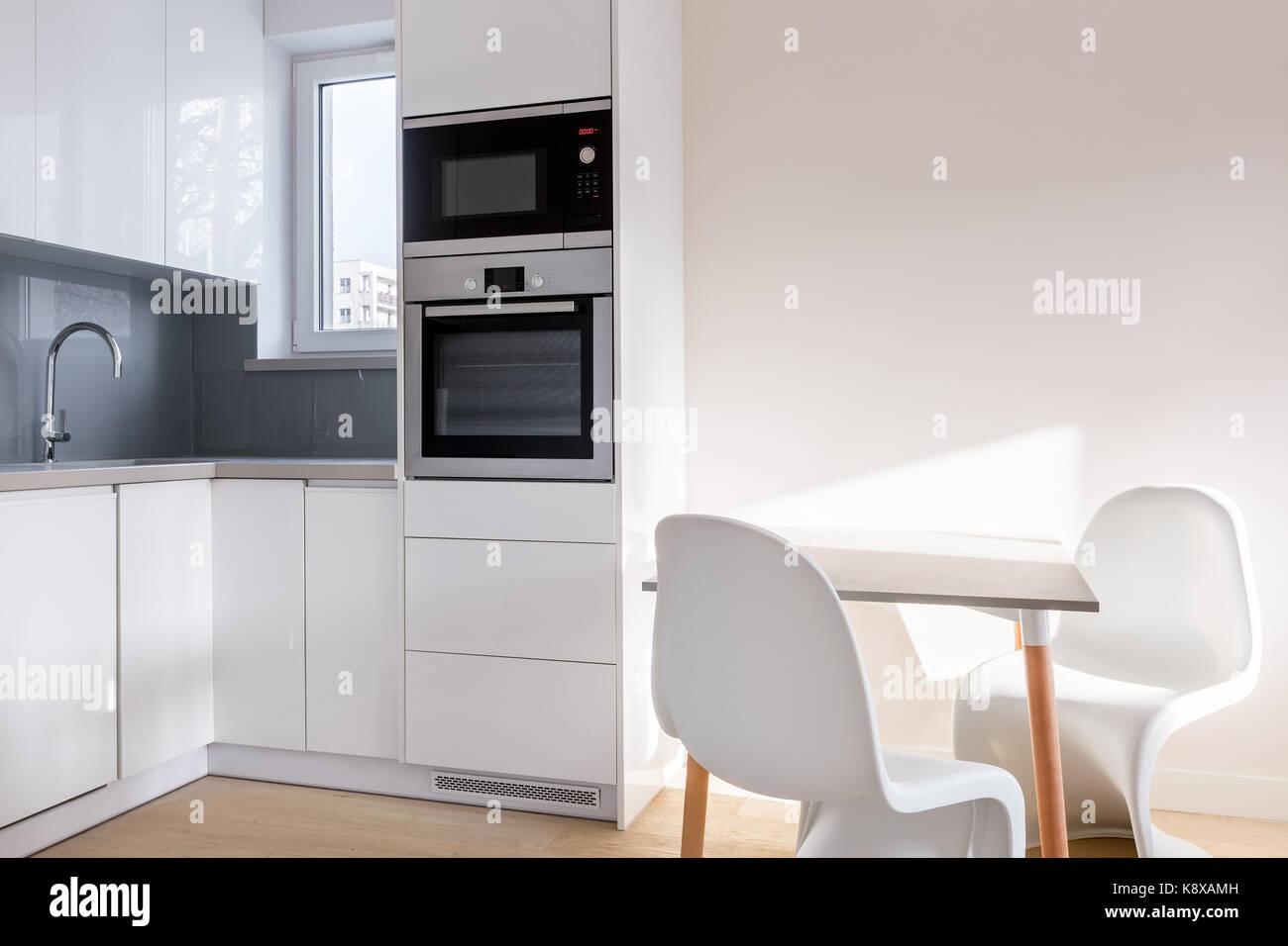 Cocina blanca con mesa y dos sillas modernas Foto & Imagen De Stock ...