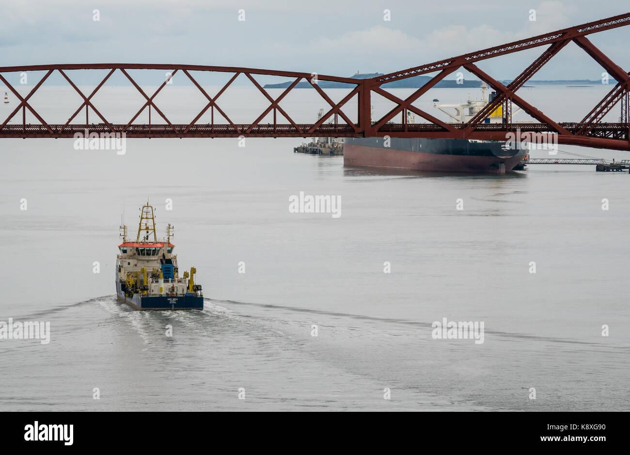 UKD Orca, una draga de tolva de aspiración de vela en voladizo bajo el puente ferroviario de Forth en aguas Imagen De Stock