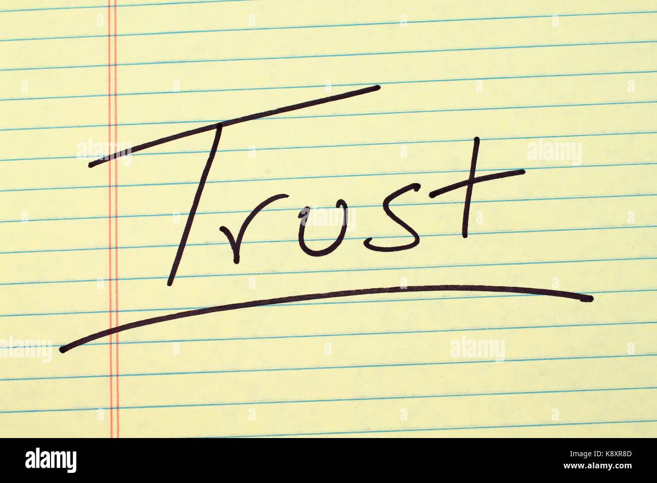 La palabra 'confianza' subrayó en un bloc de notas de papel amarillo Imagen De Stock
