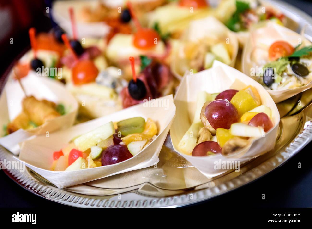Canapés caseros sandwiches pequeños aperitivos. Mezcla de diferentes finger food bocadillos para una fiesta o banquete en una placa. Foto de stock