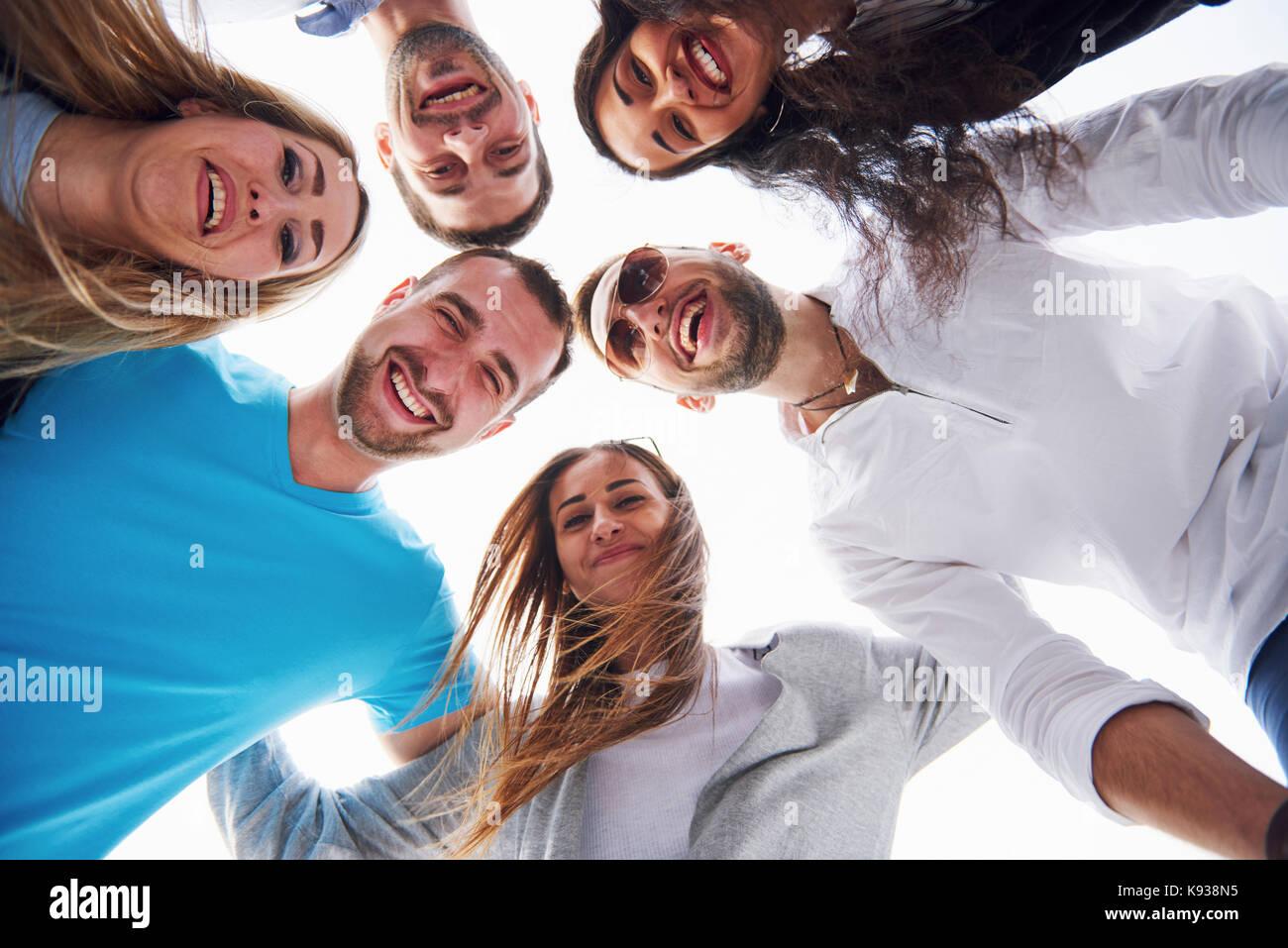 Retrato de un grupo de jóvenes sentados en el borde del muelle, en la naturaleza. amigos disfrutando de un Imagen De Stock
