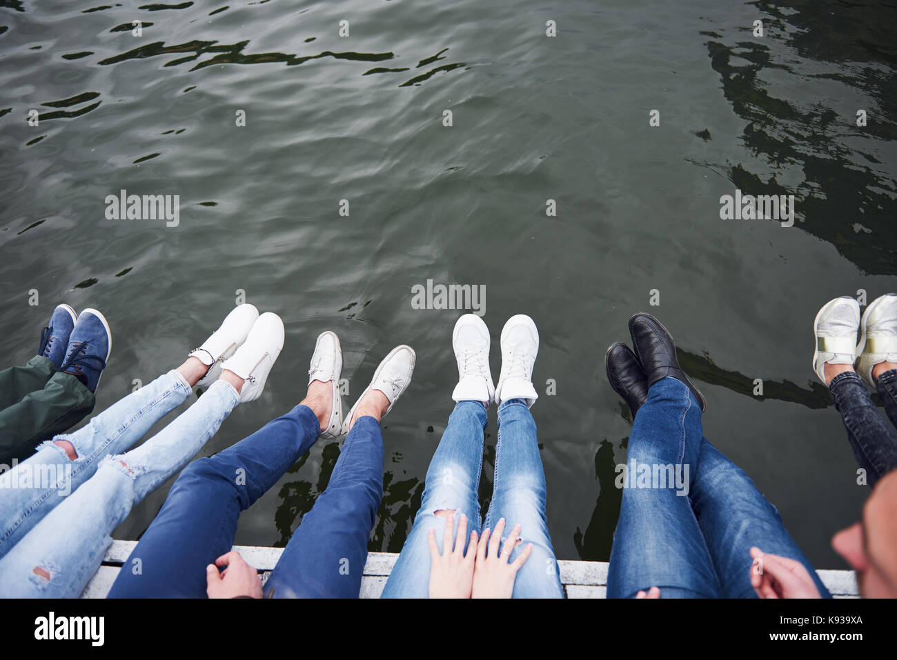 Los jóvenes amigos sentado en el puente del río, estilo de vida, los pies en el agua azul Imagen De Stock