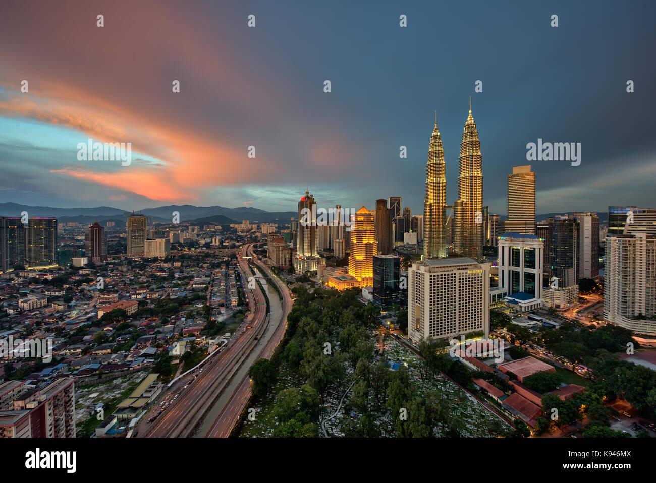 Paisaje urbano de Kuala Lumpur, Malasia, al atardecer, con torres Petronas iluminada en la distancia. Foto de stock