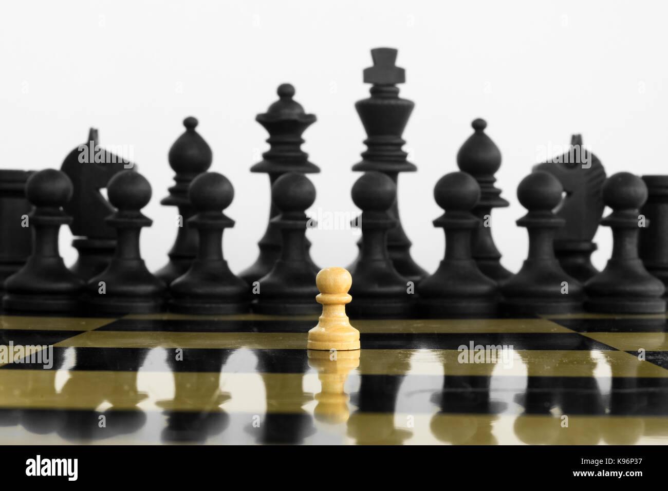 La auto-confianza Peón blanco delante de un ejército negro de ajedrez antes del enfrentamiento. Imagen De Stock