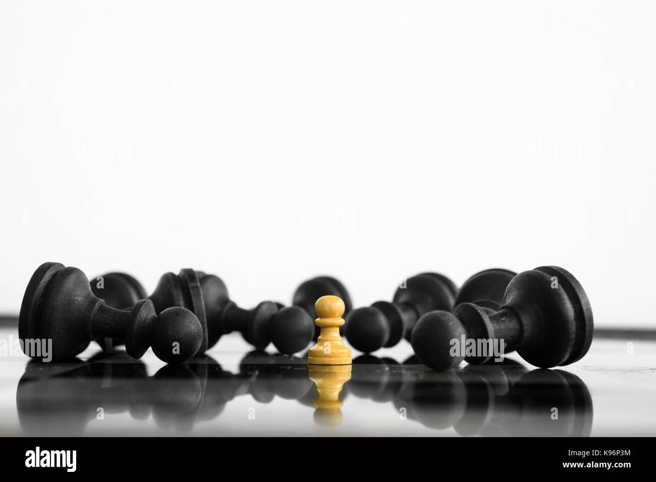 Peon blanco victoriosa de pie delante de un derrotado ejército negro de ajedrez después del enfrentamiento. Imagen De Stock