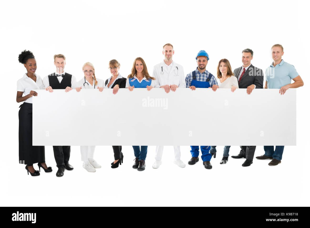 Retrato de grupo de personas con diversas ocupaciones la celebración de Billboard en blanco contra el fondo Imagen De Stock