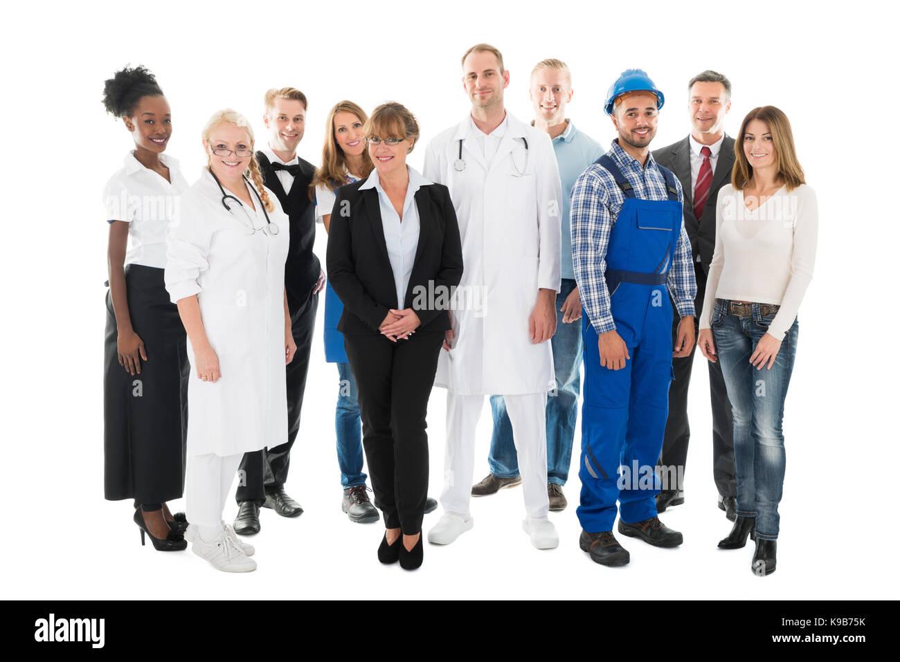 Retrato de grupo de seguros de personas con diversas ocupaciones de pie contra el fondo blanco. Imagen De Stock