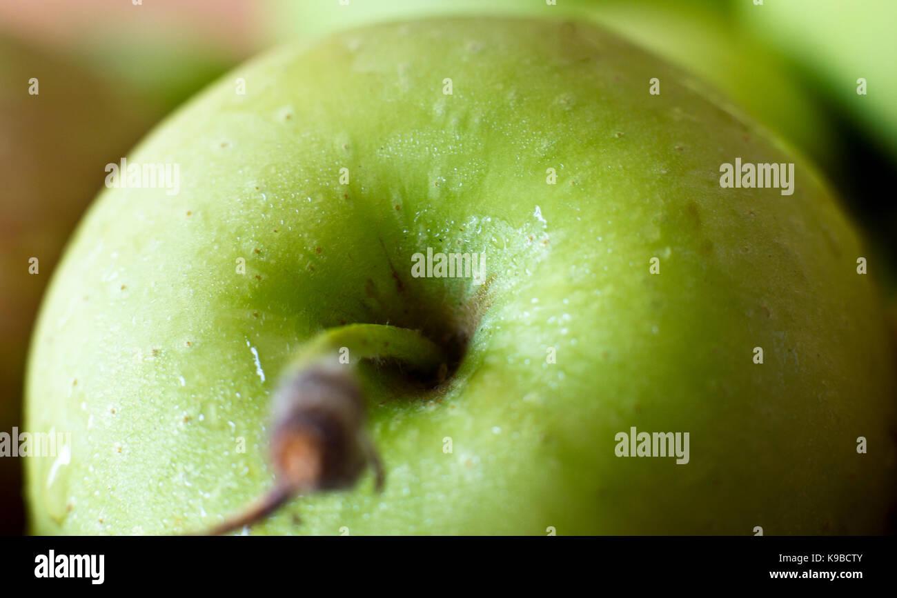Una manzana verde en las gotas de agua. macro. El enfoque selectivo. Imagen De Stock