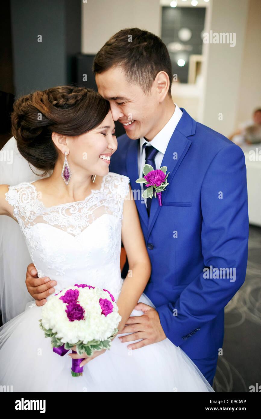 Encantadora pareja de la novia y el novio en el vestíbulo riendo y genuinamente sonrientes retrato positivo. Imagen De Stock
