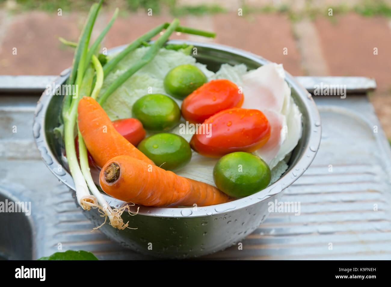 Verduras (Galés cebollas, zanahorias, tomates, repollo chino) y frutas (limones), mezclado, frescas bañadas Imagen De Stock