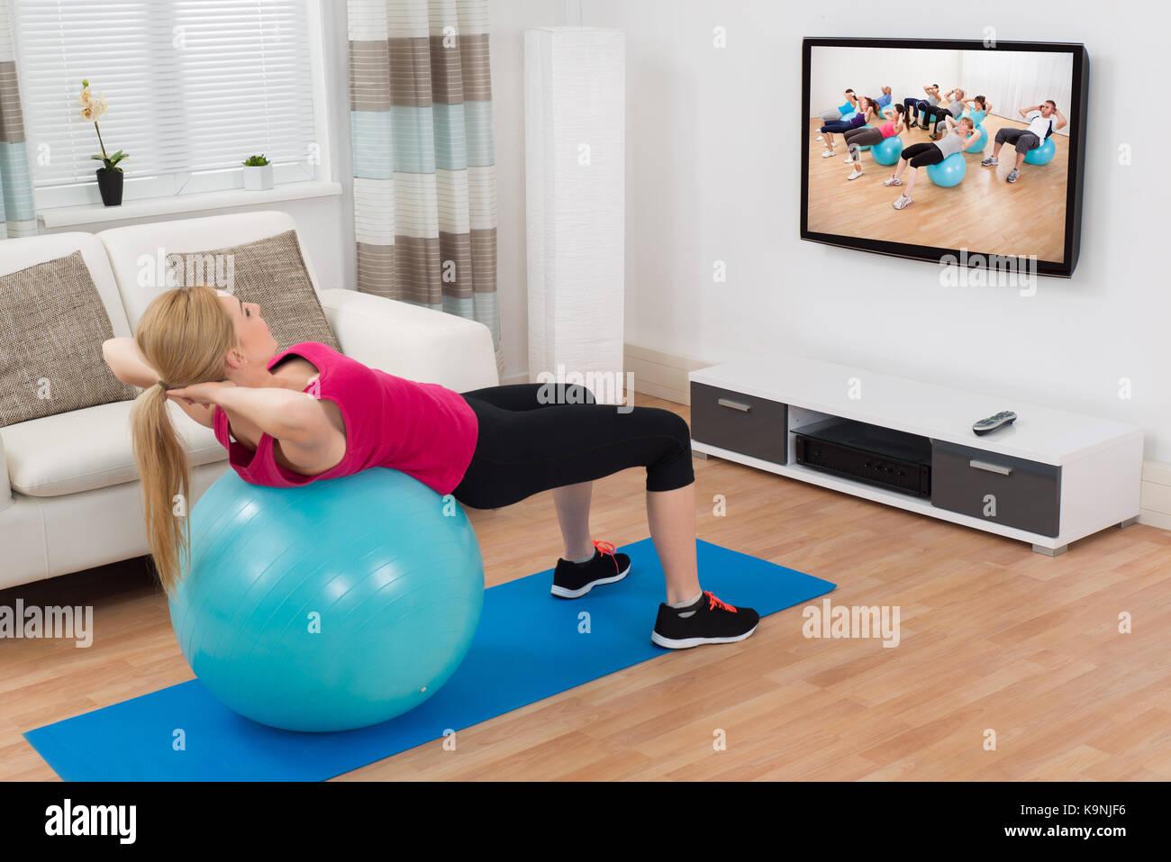 Mujer joven hacer ejercicio con pelota fitness azul mientras está viendo el programa de televisión Imagen De Stock