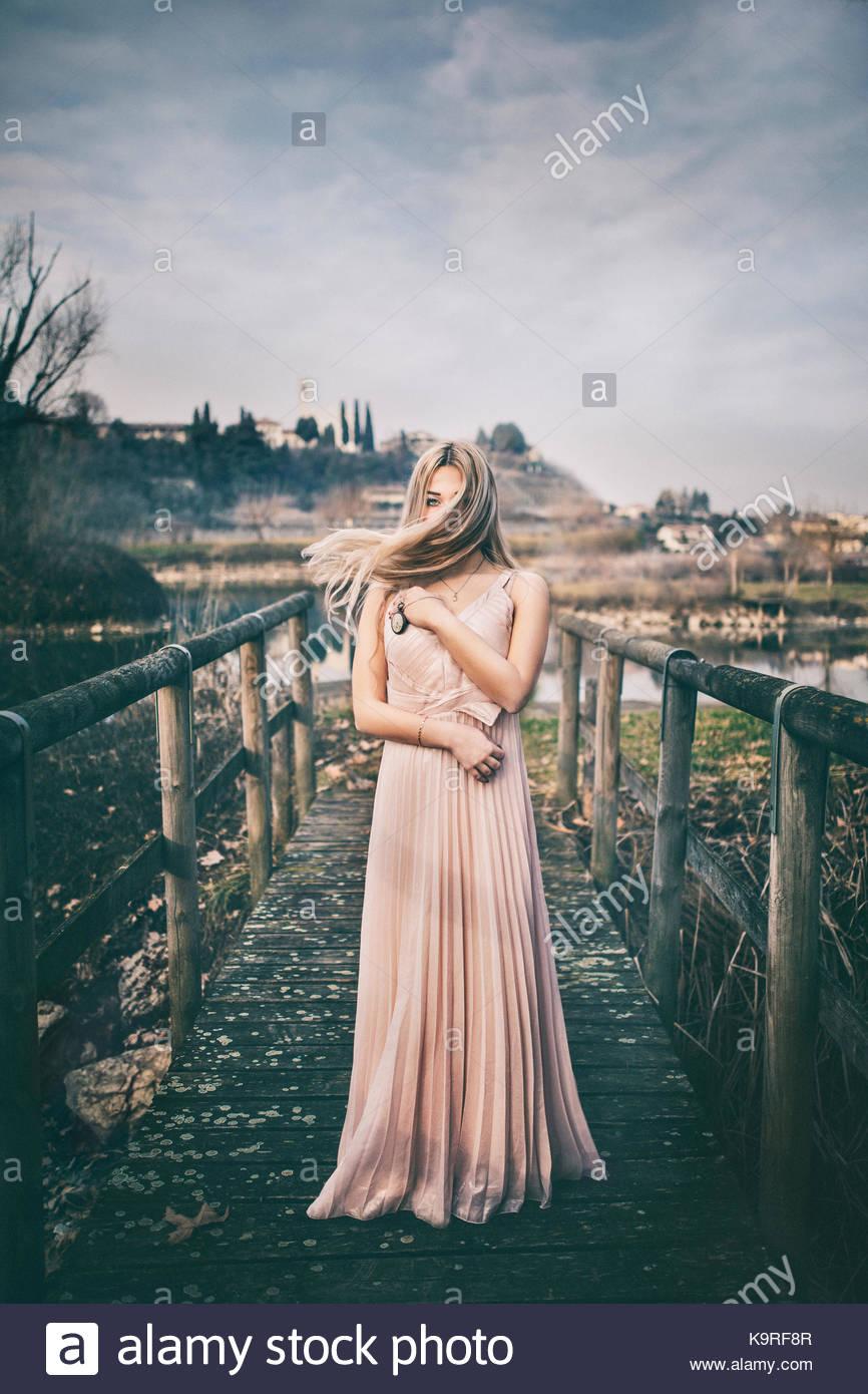 Retrato de una niña de pie cerca de un estanque. El cabello se está moviendo. Pelo rubio. Parece de ensueño. Imagen De Stock