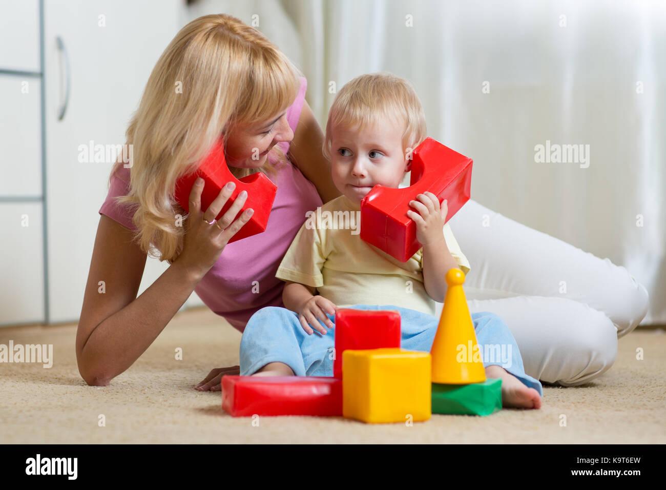 La madre y el niño chico lindo papel jugar juntos en casa Foto de stock