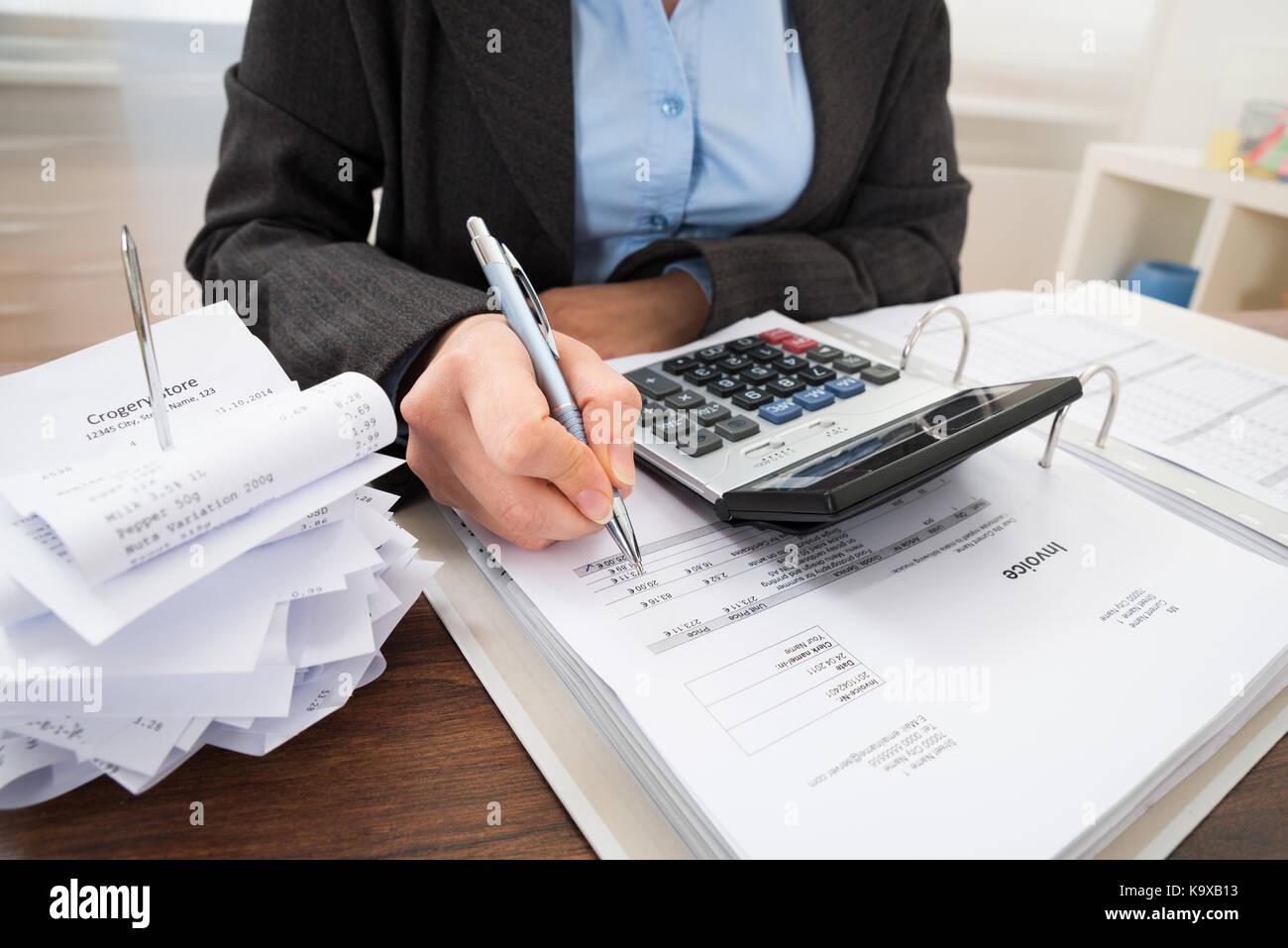 Close-up de comerciantes calcular las facturas en la mesa Imagen De Stock