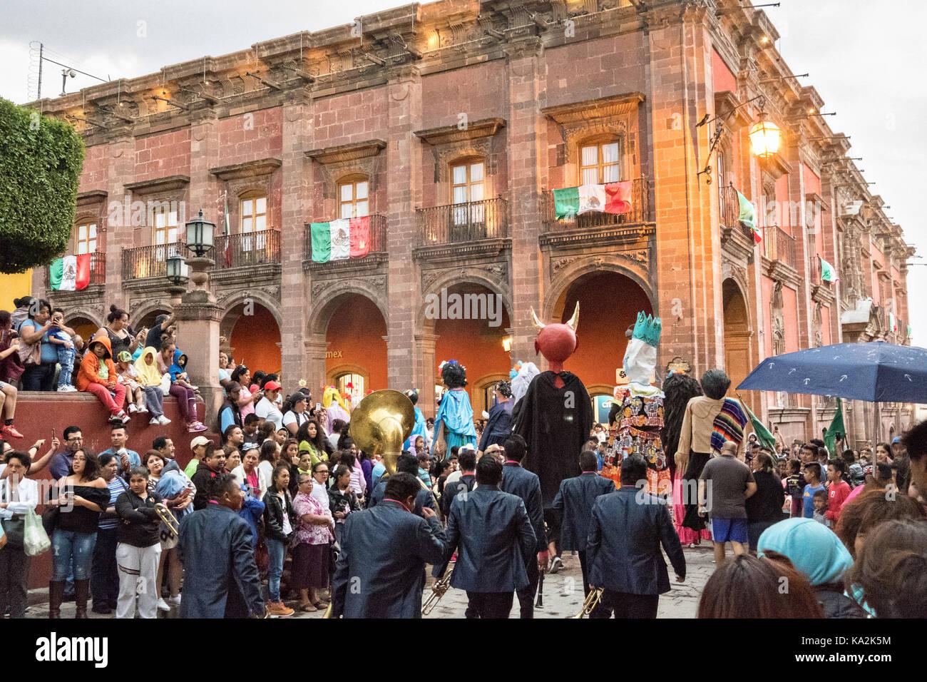 Un Marching Band sigue un desfile de gigantes de papel maché llamados mojigangas títeres en una procesión por la ciudad al comienzo de la semana de la fiesta de la patrona de San Miguel el 22 de septiembre de 2017 en San Miguel de Allende, México. Foto de stock