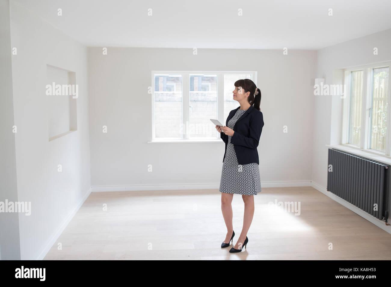 Agente inmobiliario hembra con tableta digital mirar alrededor de bienes vacantes para la valoración Imagen De Stock