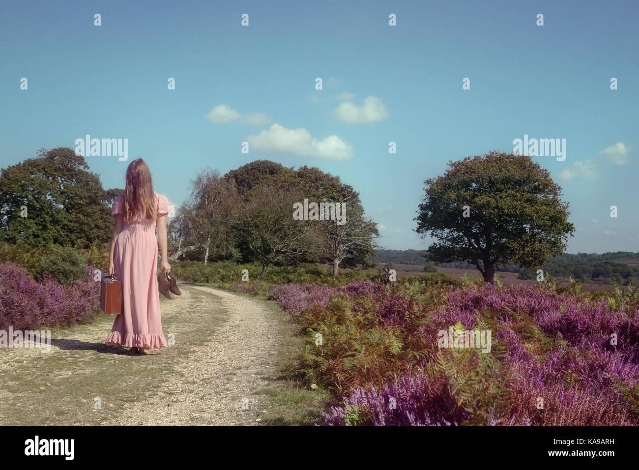 Una mujer en un vestido de púrpura es caminando a través de los brezos con una maleta Foto de stock