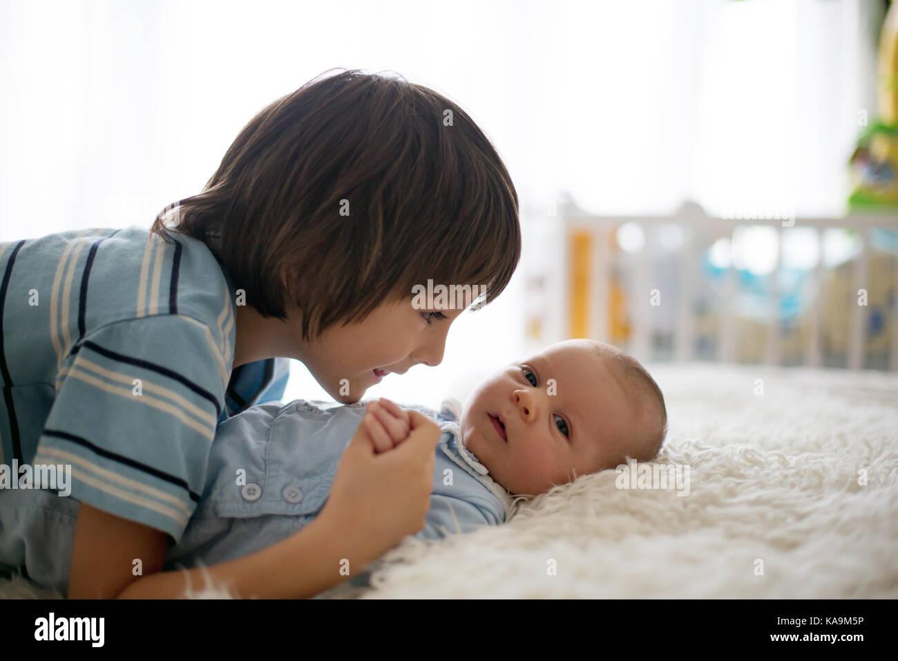 Hermoso muchacho, abrazando con ternura y el cuidado de su bebé recién nacido hermano en casa. La familia Imagen De Stock