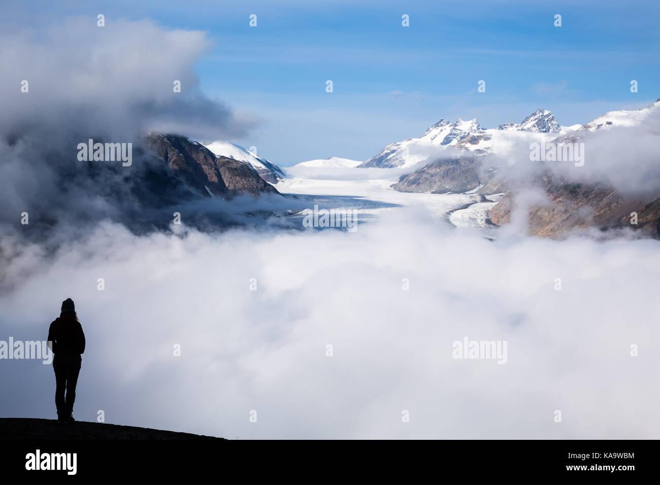 Justo después del amanecer, un salmón niebla picos del glaciar desde detrás de las nubes. El sol Imagen De Stock