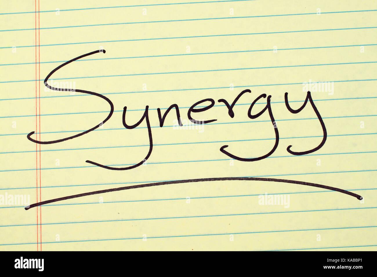 """La palabra """"SINERGY"""" subrayó en un bloc de notas de papel amarillo Imagen De Stock"""