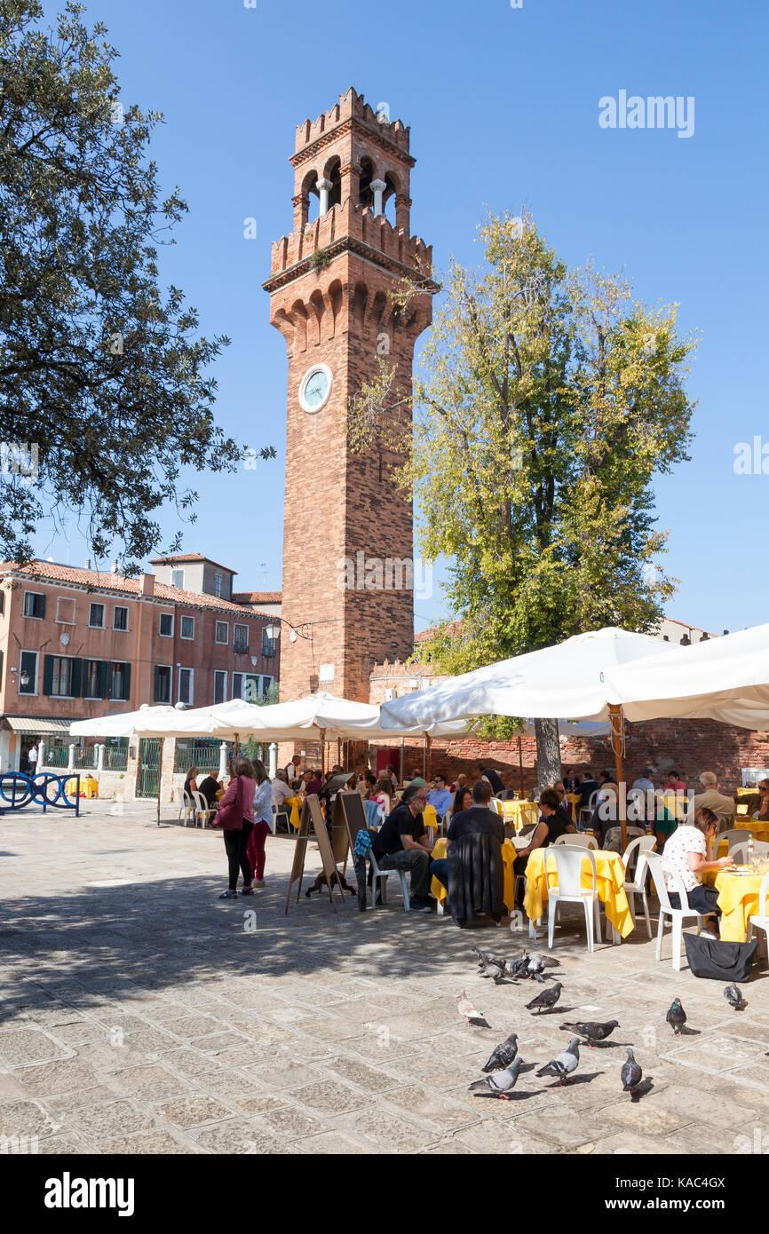 Los turistas comiendo en el Campo Santa Stefano, Murano, Venecia, Italia bajo el paraguas al aire libre con la torre Imagen De Stock