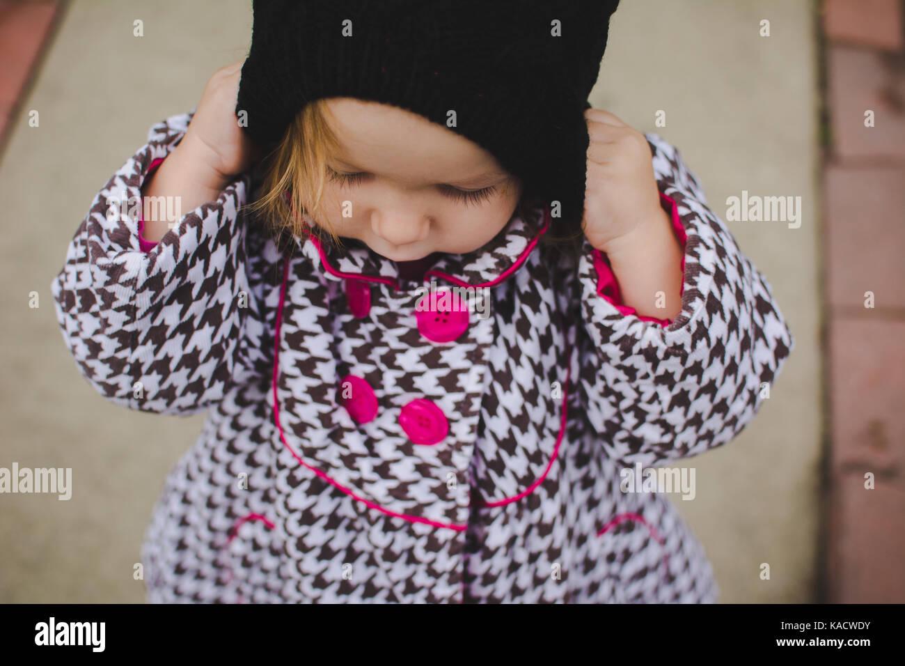 Un niño ajustando su sombrero tejido de invierno. Imagen De Stock