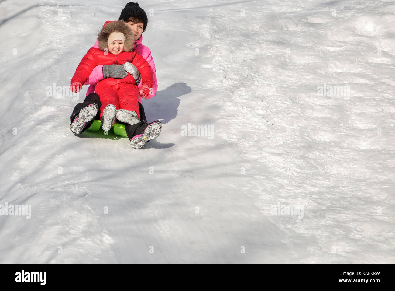 Feliz madre y su hija disfrutando de un paseo en trineo abajo de las colinas, juegos de invierno y diversión. Imagen De Stock