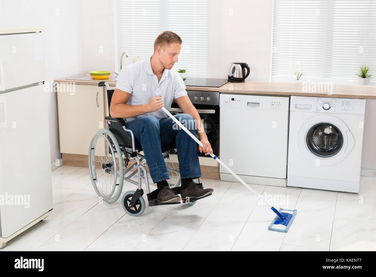Hombre minusválido en silla de ruedas piso de limpieza con el MOP en ...