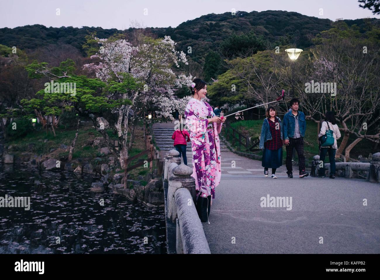 Cada día escena callejera en Japón. Las mujeres japonesas en kimono tradicional haciendo un selfie junto Imagen De Stock