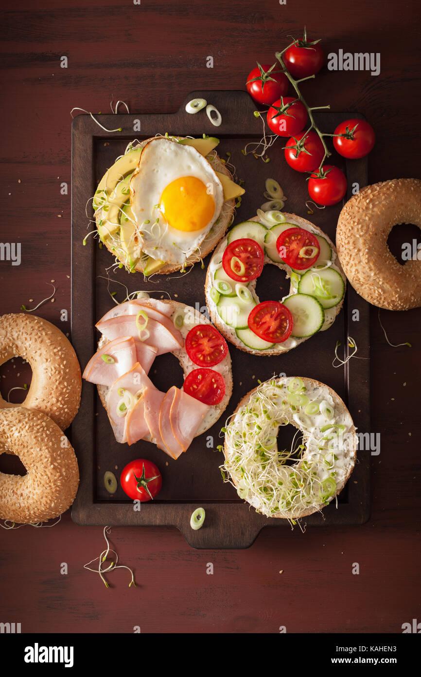 Variedad de sándwiches en bagels: huevos, jamón, tomate, aguacate, queso de pasta blanda, los brotes de Imagen De Stock