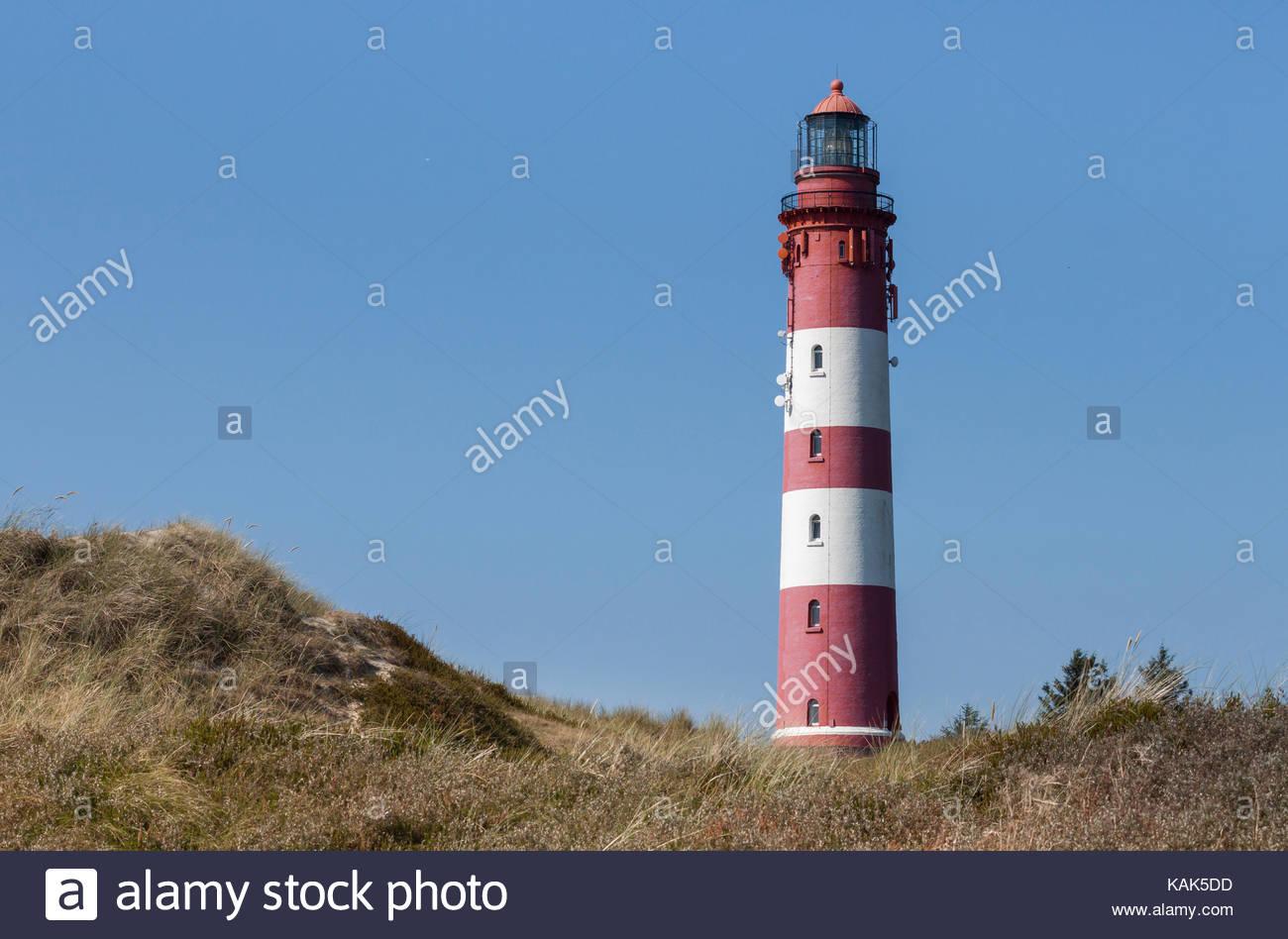 Faro con franjas rojas y blancas. Las dunas de arena en el primer plano, un cielo azul sin nubes, isla Amrum en Imagen De Stock