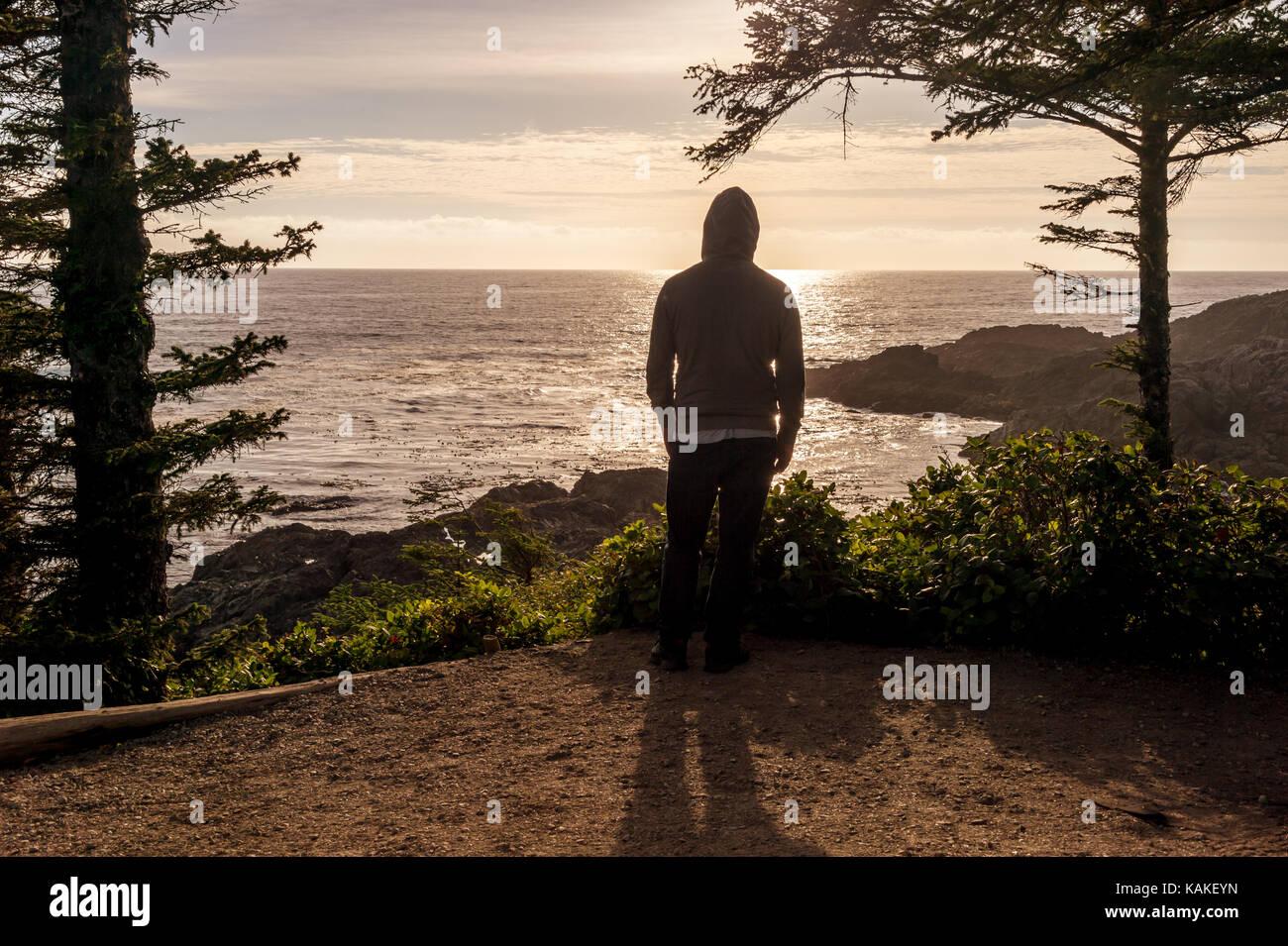 Hombre de pie con vistas al mar en la isla de Vancouver al atardecer Foto de stock