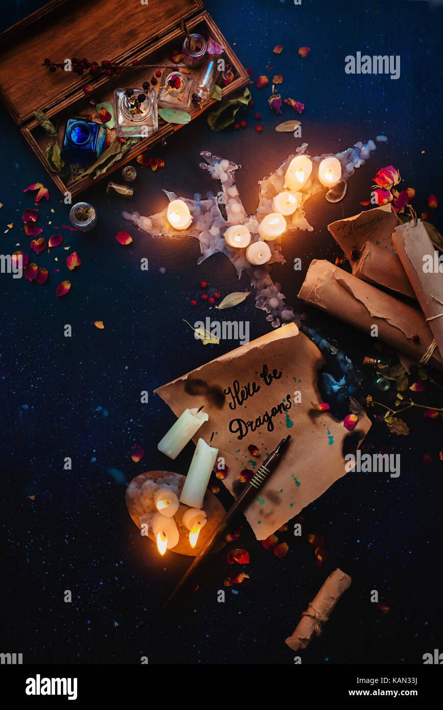 Fantasy bodegón con un dragón de la llama de una vela, pergaminos de hechizos, hierbas, frascos de pociones Imagen De Stock