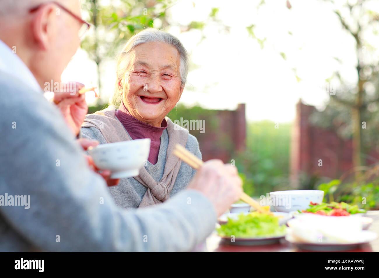 Feliz y saludable chino superior par juntos a comer en el jardín Imagen De Stock