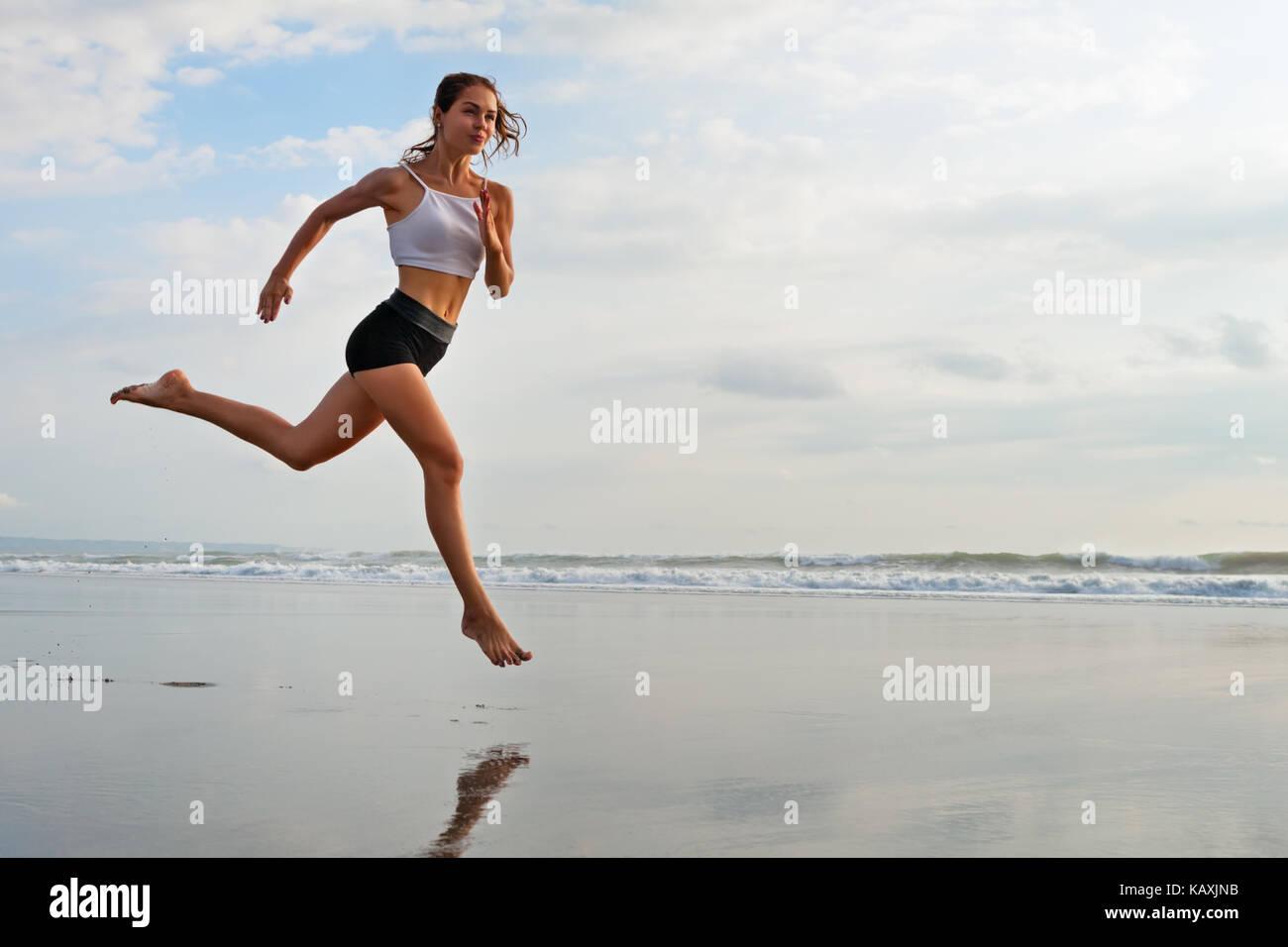 Barefoot deportivo chica con cuerpo delgado que corre a lo largo de navegar por la piscina de agua de mar para mantenerse Imagen De Stock
