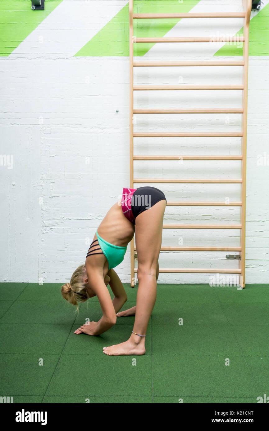 d70bb385a Chica fitness estirar las piernas haciendo pilates estira la pierna  ejercicios en el gimnasio. atleta ejercer abductor músculo flexor de la  cadera .
